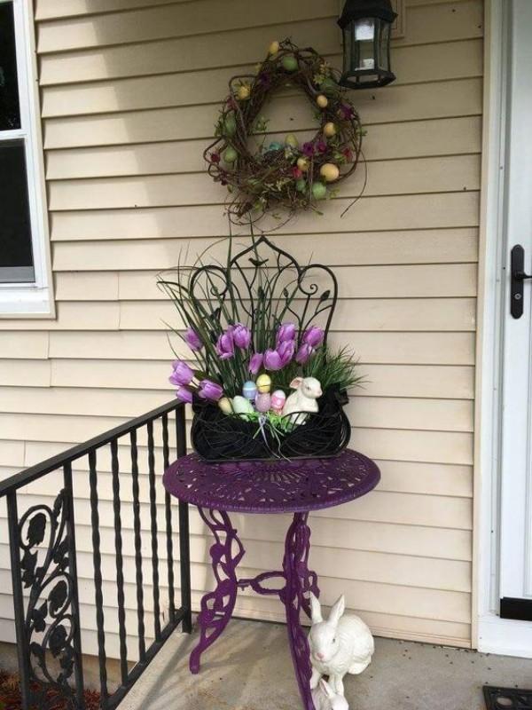 Osterdeko draußen kleine Veranda bunt dekoriert lilafarbener runder Tisch weiße Hasen lila Tulpen Kranz