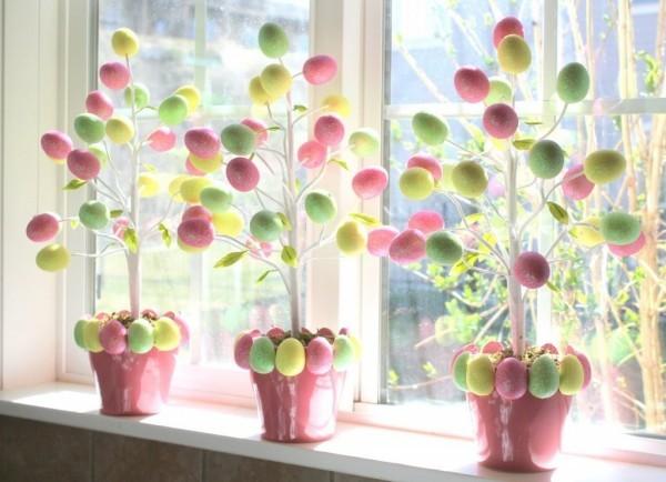 Osterdeko draußen selbstgemacht drei Töpfe mit aufgehängten bunten Eiern