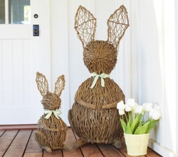 Osterdeko draußen zwei Hasen aus verflochtenen Zweigen weißer Topf weiße Tulpen