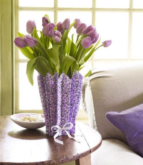Tulpen im Interieur Flieder Farbe Vase mit Umschlag auf rundem Tisch neben Sofa