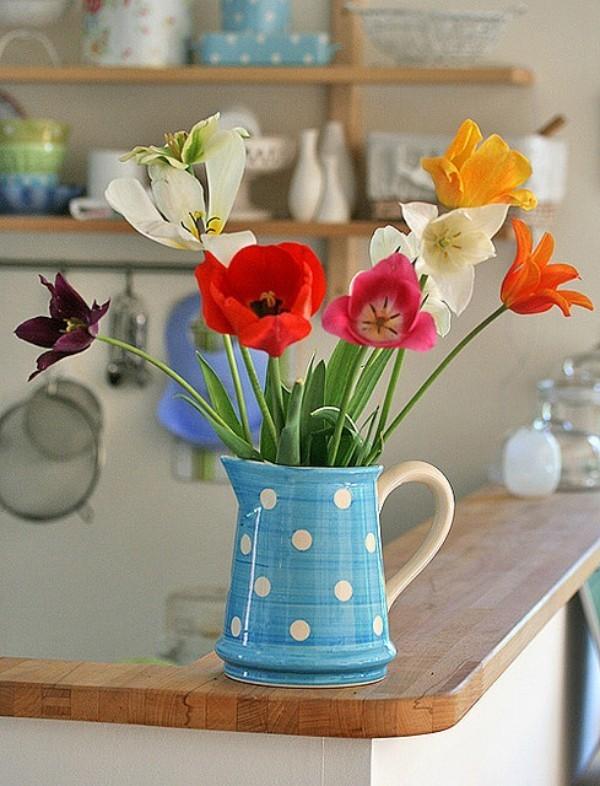 Tulpen im Interieur mehrfarbige Blüten in blauer Retro-Kanne