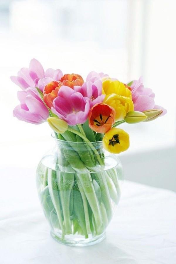Tulpen im Interieur verschiedenfarbige Blüten in runder Vase aus Glas