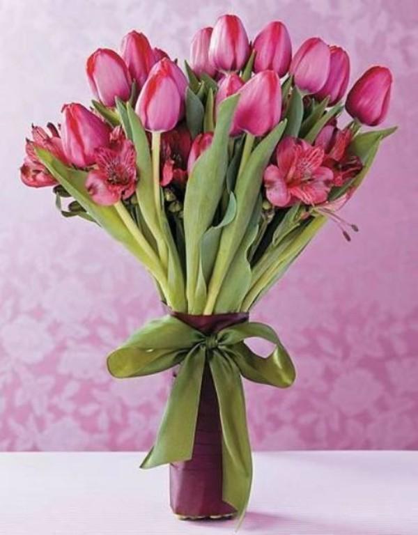 Tulpen im Interieur violette Blüten violetter Hintergrund Vase grüne Schleife