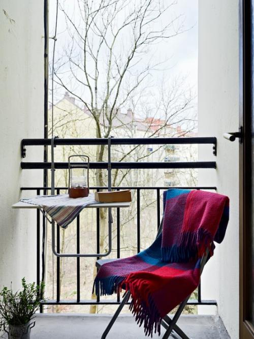 Balkon Ideen kleinen Balkon gestalten warme Wurfdecke gesättigte Farben visuellen Akzent setzen