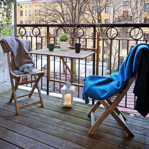 Balkon Ideen kleinen Balkon gestalten warme Wurfdecken dekorative Laterne Kerze