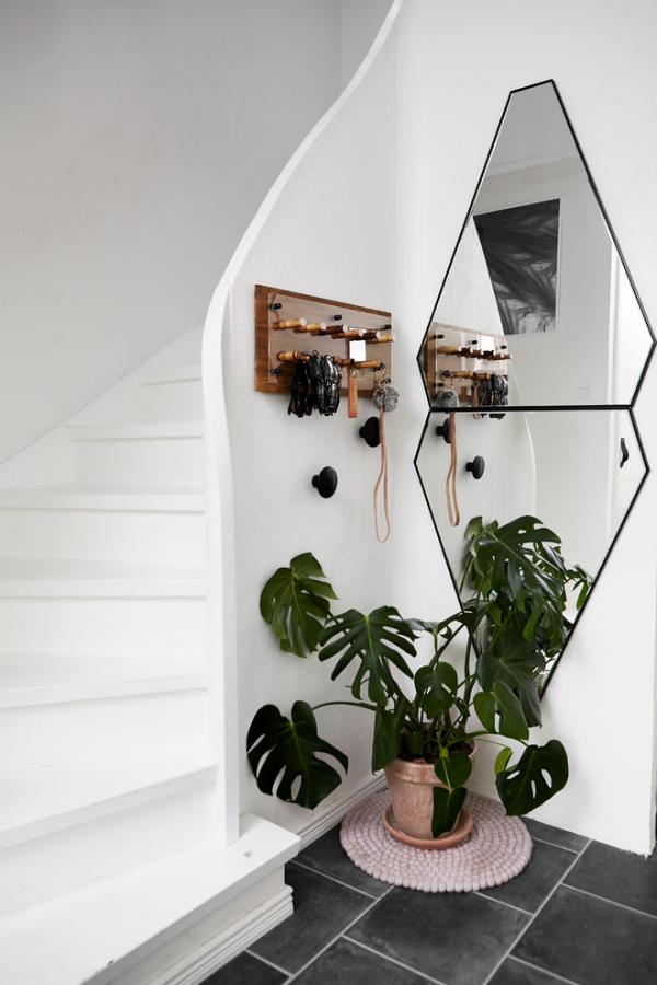 Dekorative Wandspiegel im Flur Treppenhaus weißes Design ausgefallene Spiegelform frische Grünpflanze