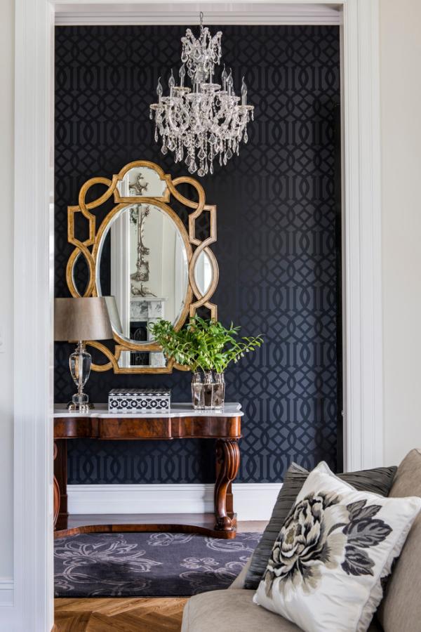 Dekorative Wandspiegel im Flur dunkelblauer Hintergrund ausgefallene Spiegelform Lampe Kristallkronleuchter
