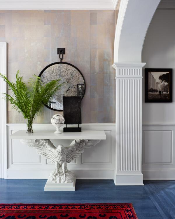 Dekorative Wandspiegel im Flur klassisches Design Adlerfigur als Tischbein weißer Tisch Farn runde Spiegelform