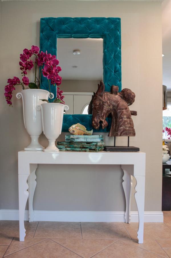 Dekorative Wandspiegel im Flur klassisches Design dunkler Rahmen weißer Tisch Vase Deko Figur