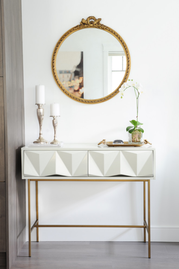 Dekorative Wandspiegel im Flur runde Form schlichtes Design weiße Kerzen Topfblume