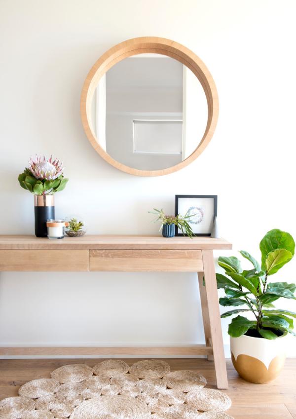 Dekorative Wandspiegel im Flur runder Spiegel Holzrahmen heller Holztisch frisches Grün