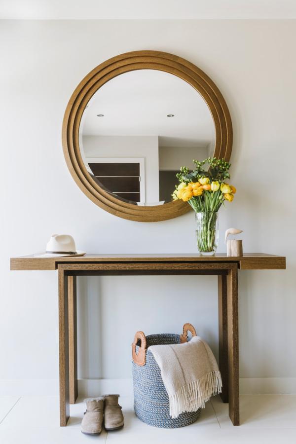 Dekorative Wandspiegel im Flur schlichtes Design runde Form Blumen in Vase