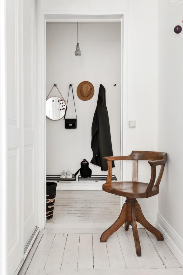 Dekorative Wandspiegel im Flur schlichtes Design runder kleiner Spiegel Stuhl im Vordergrund