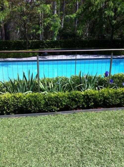 Zaun um Pool Ideen aus Metall mit zahlreichen Grünpflanzen