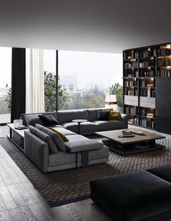 Maskulin und elegant modernes Wohnzimmer bequeme graue Möbel modernes Bücherregal interessante Beleuchtung