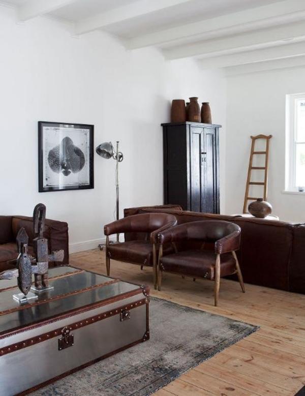 Maskulin und elegant modernes Wohnzimmer natürliche einfache Einrichtung zwei Ledersessel viel Licht Deko Figuren