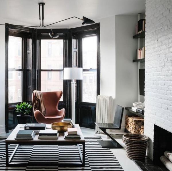 Maskulin und elegant modernes Wohnzimmer weiß gestrichene Ziegelwand Egg Chair aus Leder als Akzent