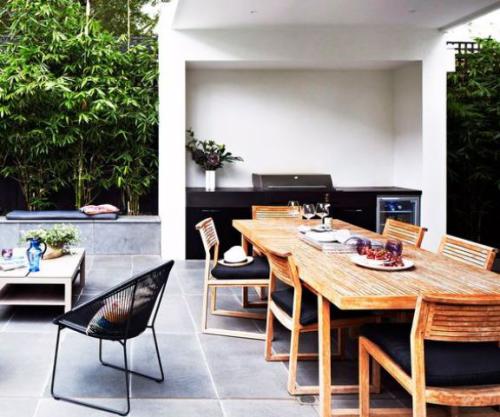 Outdoor Küche in Schwarz gestaltet klein unter Dach langer Esstisch viele Stühle