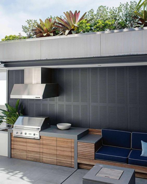 Outdoor Küche modern eingerichtet und gestaltet Grillgerät Abzugshaube Edelstahl Beton Teakholz
