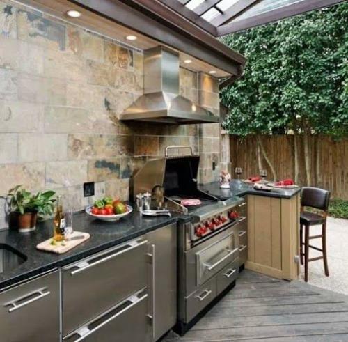 Outdoor Küche voll ausgestattet Steinwand moderne eingebaute Küchengeräte Abzugshaube
