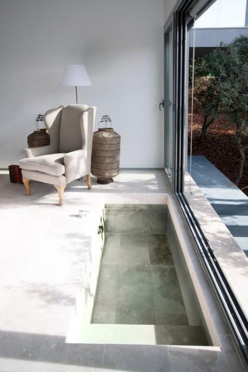Eingelassene Badewanne einfaches Design jedoch sehr ansprechend Glasschiebewand zum Garten