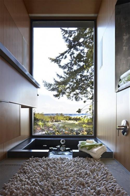 Eingelassene Badewanne flauschiger Badeteppich Blick zum Garten