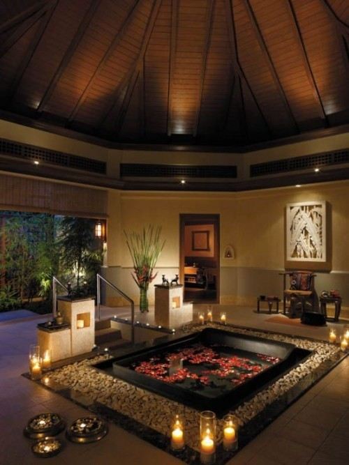 Eingelassene Badewanne großer Raum quadratische Form Rosenblüten Kieselsteine