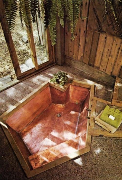 Eingelassene Badewanne mehreckige Form Holzwand grüne Pflanzen Farne