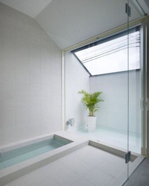 Eingelassene Badewanne minimalistisch gestaltet weiß dominiert Bergpalme als Akzent