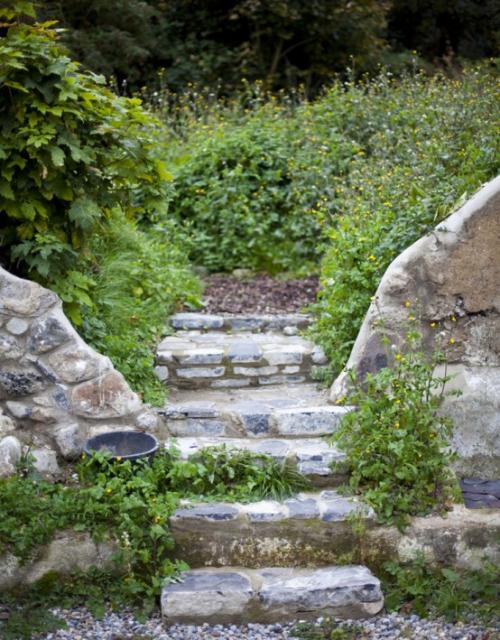 Gartenwege aus Stein Naturgarten dicke Trittplatten aus Stein pflanzenbewachsen
