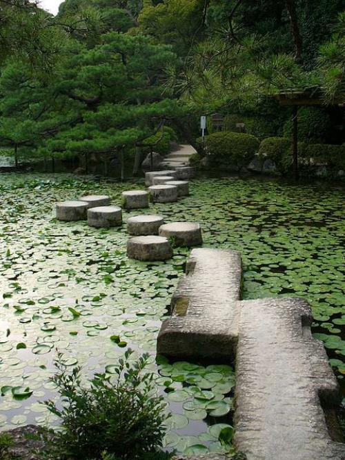 Gartenwege aus Stein auf dicken stabilen Steinen den Gartenteich überqueren
