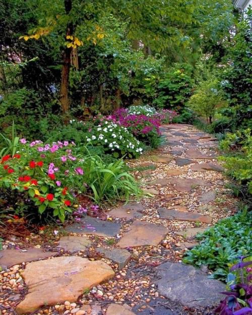 Gartenwege aus Stein große Steinplatten Kies viele bunte Blumen beiderseits