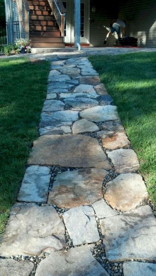 Gartenwege aus Stein in gerader Linie direkt zum Haus große Steinplatten etwas Splitt