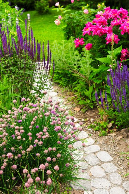 Gartenwege aus Stein kopfsteingepflasterter Pfad schöne bunte Blumen