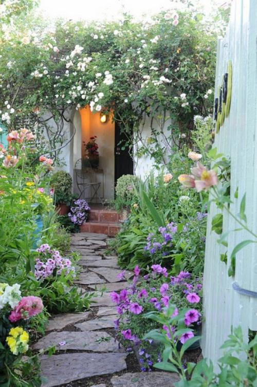 Gartenwege aus Stein mit Steinplatten belegt von Sonnenblumen umgeben führt direkt zum Hauseingang