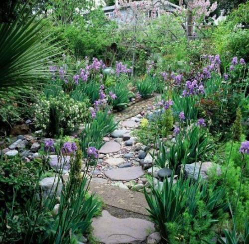 Gartenwege aus Stein schmaler Pfad viele bunte Blumen beiderseits