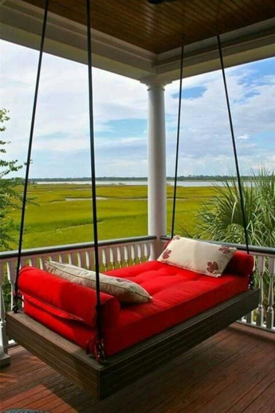 Hängebett draußen auf der überdachten Terrasse rote Polsterung zwei Deko Kissen herrlicher Panoramablick auf die grüne Landschaft