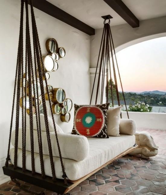 Hängebett draußen auf der überdachten Veranda im Boho Stil Kissen runde Spiegel als Wanddekoration