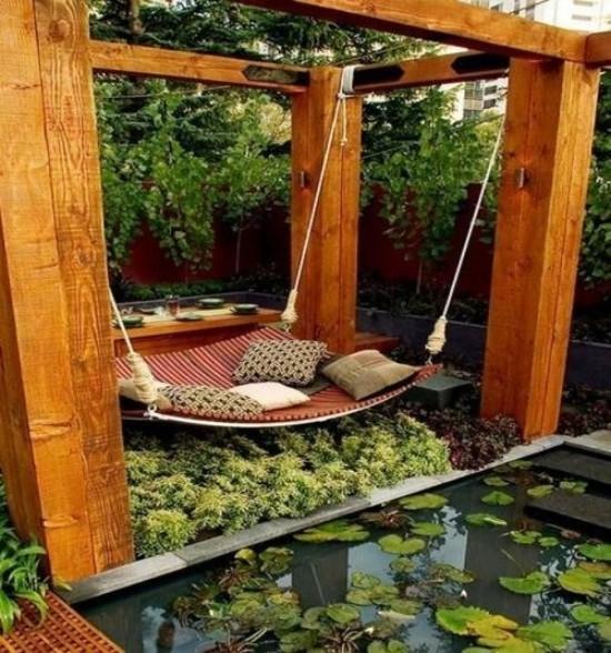 Hängebett draußen ausgefallenes Design im japanischen Stil direkt am Teich viele grüne Pflanzen Deko Kissen