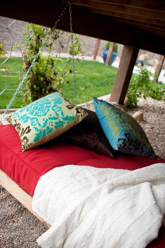Hängebett draußen bunte Kissen als Deko grüner Garten im Hintergrund