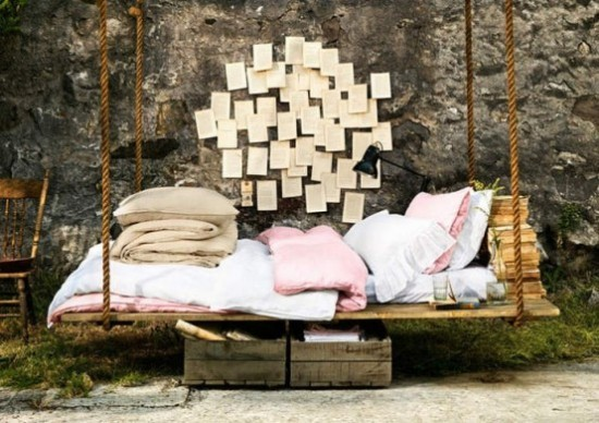 Hängebett draußen im Garten Bücher zum Lesen Bettwäsche zum Schlafen Steinwand mit Zetteln Papier dekoriert