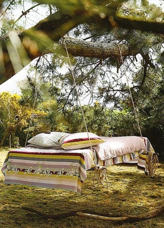Hängebett draußen im Garten an einem Baum aufgehängt in Boho Stil wirkt einladend