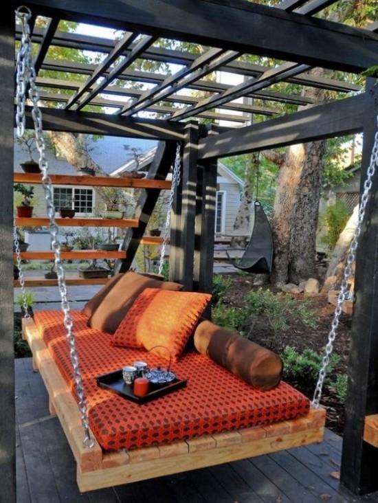 Hängebett draußen im Garten orangenfarbene Polsterung ein Tablett mit Kaffeetassen Kerze darauf
