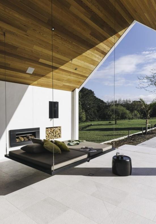 Hängebett draußen in Doppelausführung auf der überdachten Veranda vor eingebautem Kamin runder Beistelltisch