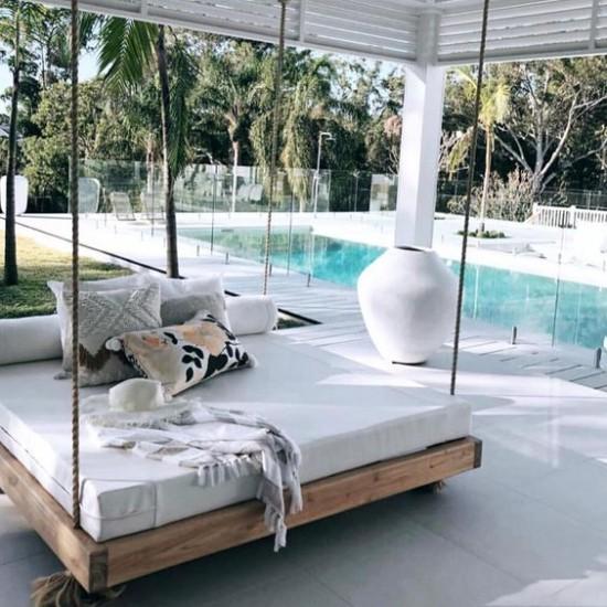 Hängebett draußen neben dem Pool Seemannseile Deko Kissen viel Grün ringsherum