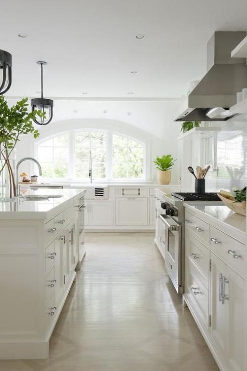 Halbkreisfenster gewölbte Zimmerdurchgänge helle sehr ansprechende Küche ganz in Weiß grüne Zimmerpflanzen als Akzent