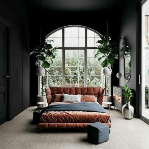 Halbkreisfenster gewölbte Zimmerdurchgänge schickes Schlafzimmer komfortables Bett dunkle Wände viel Licht vom bogenförmigen Fenster grüne Pflanzen