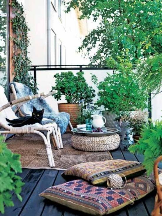 Holzterrasse gestalten Boho Style Sitzkissen schwarzer Kater viele grüne Pflanzen