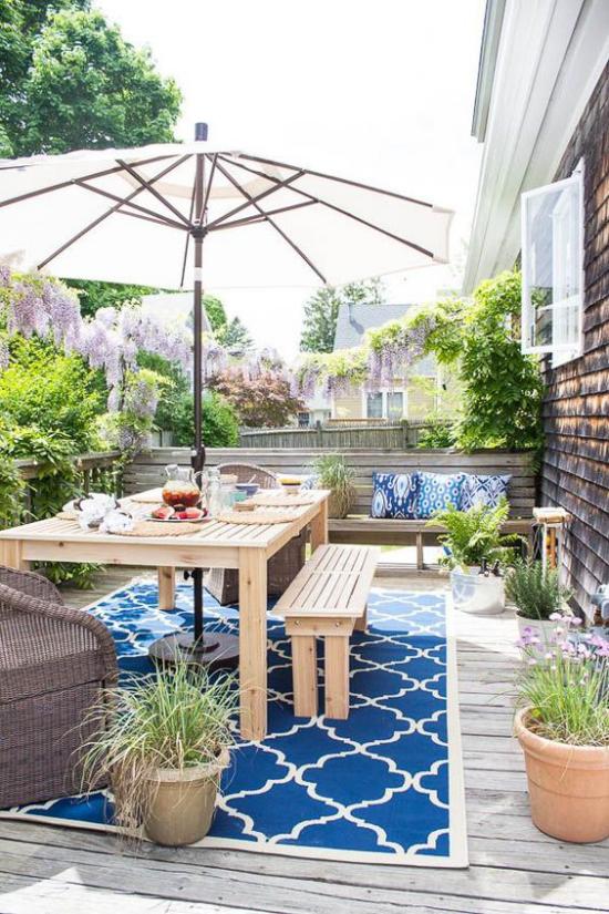 Holzterrasse gestalten Esstisch Sitzbank aus Holz großer Sonnenschirm Teppich viele grüne Topfpflanzen