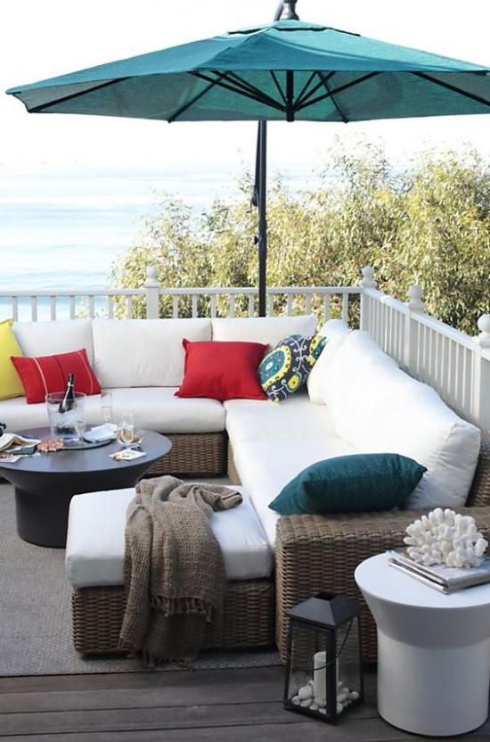 Holzterrasse gestalten Flechtmöbel weiße Sitzkissen bunte Deko Kissen Sonnenschirm